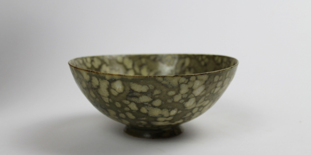 Small blossom design bowl, iron glaze with celadon markings by Ivar Mackay